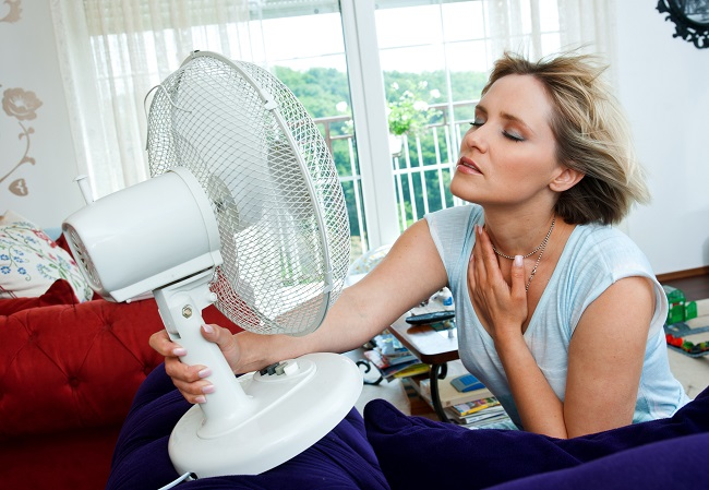 woman cooling herself with fan AirXperts Heating and Cooling Services and Repairs