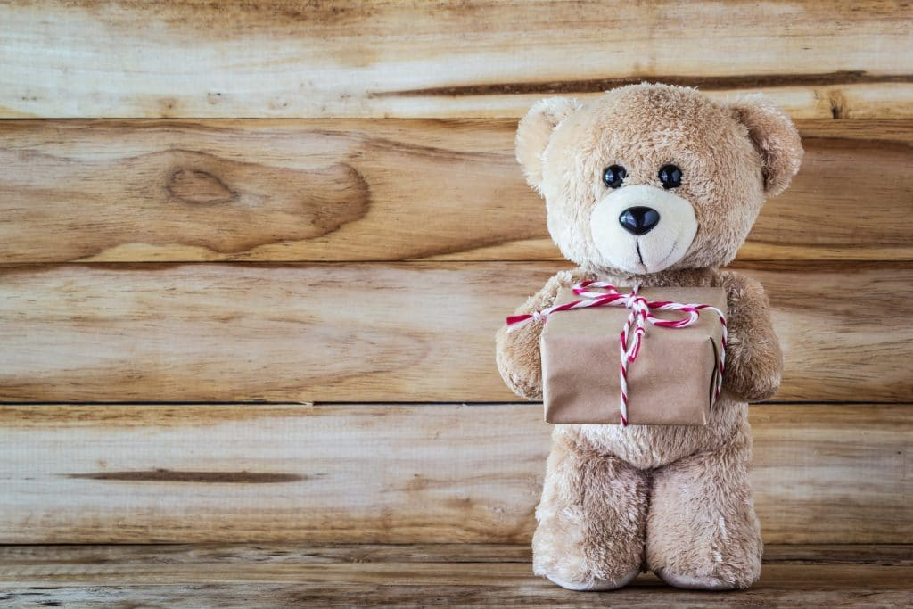A photo of teddy bear holding a gift box on plank wood board background