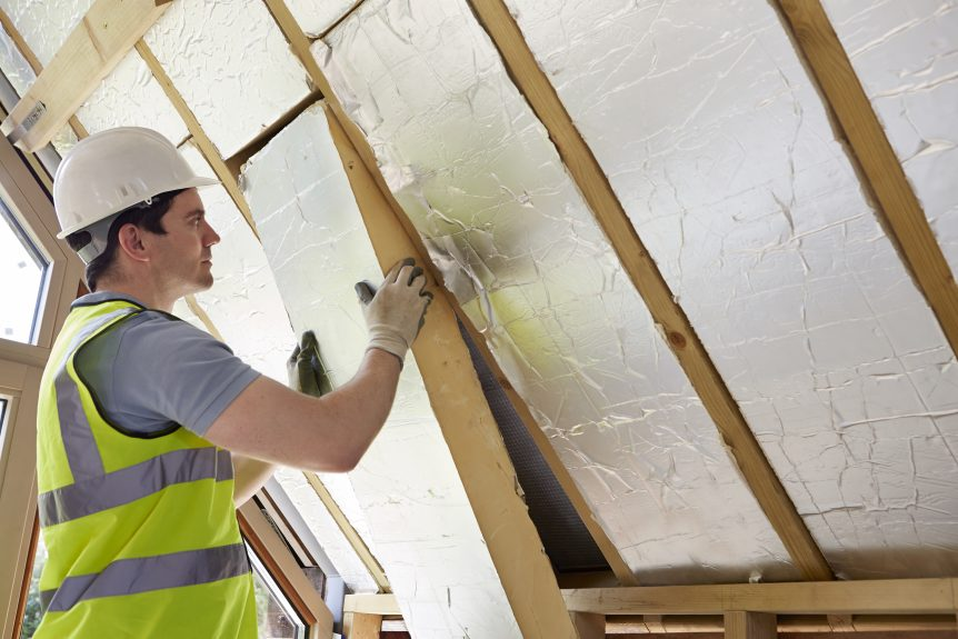 Builder Fitting Insulation Into Roof Of New Home to help with energy conservation